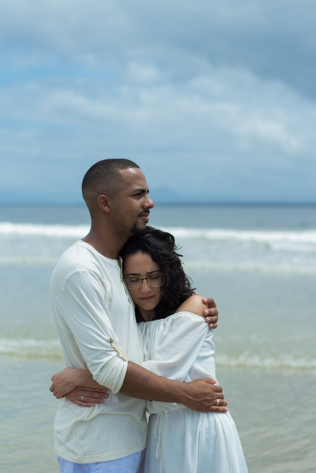 photo-of-hugging-couple-standing-by-the-beach-2378255